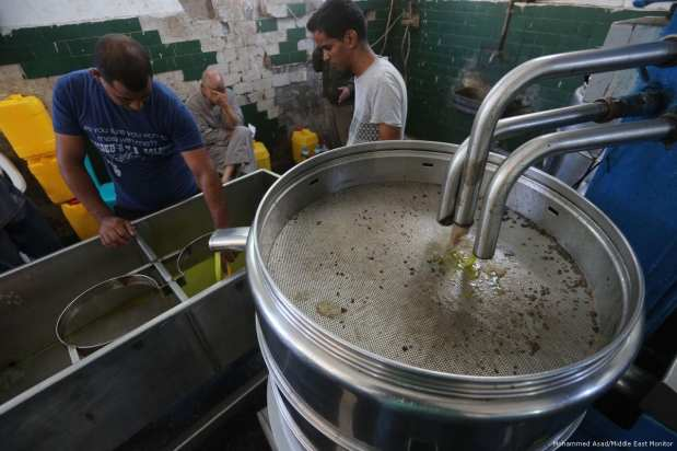 Palestinians create olive oil by compressing freshly harvested olives in Gaza on 23 October 2017 [Mohammed Asad/Middle East Monitor]
