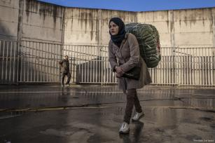 A woman can be seen carrying heavy goods on their backs across the Spanish-Moroccan border [Fernando Del Berro]