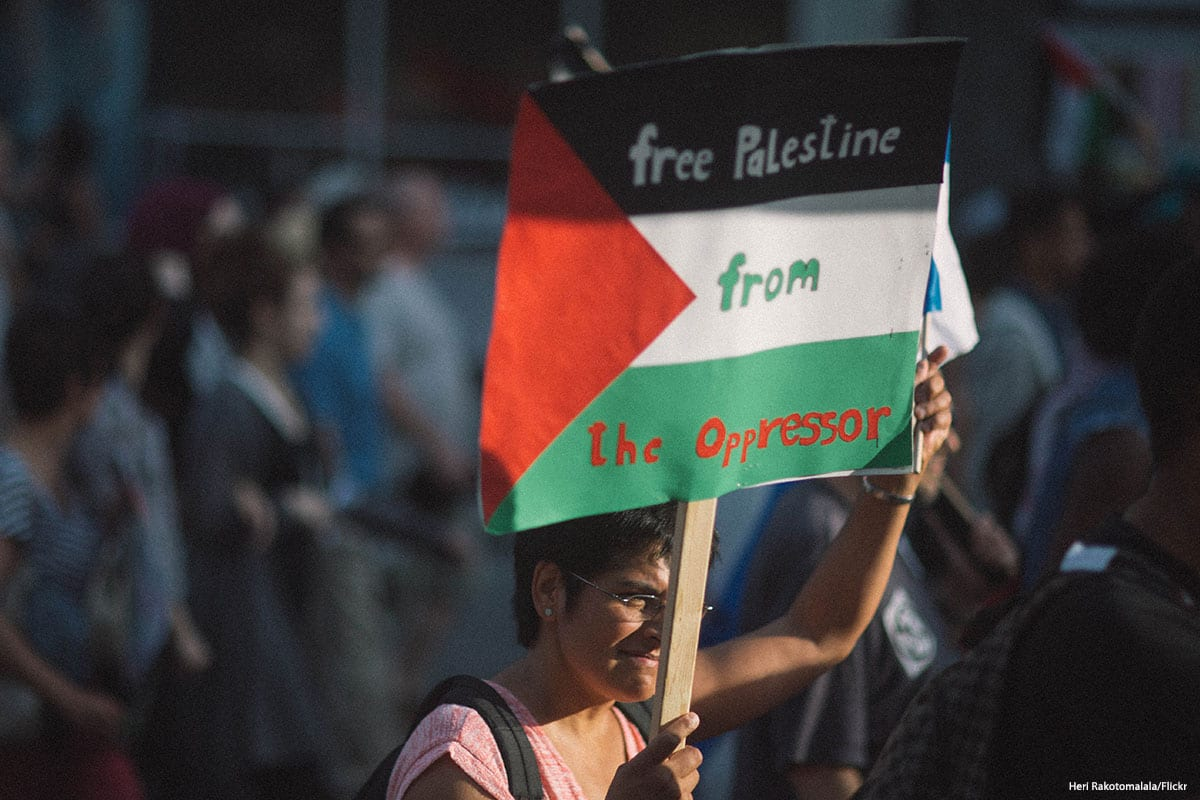 An activist holds up a placard during a protest supporting the Boycott, Divestment and Sanctions movement (BDS) [Heri Rakotomalala/Flickr]