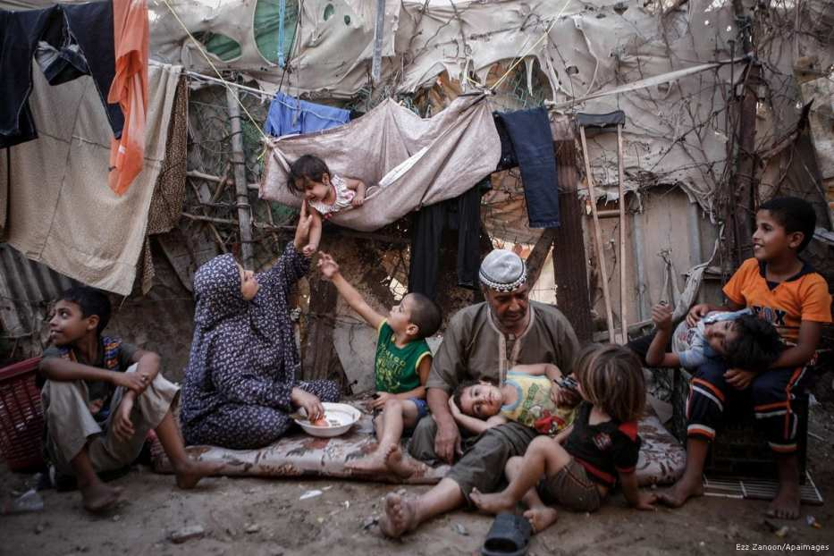 A Palestinian family can be seen outside their home in Gaza [Ezz Zanoon/Apaimages]