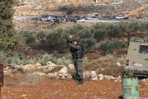 An Israeli soldier is seen as Palestinians react to Israeli soldiers after a Palestinian farmer shot dead by Jewish settlers, at the Khusra village of Nablus in West Bank on November 30, 2017. After that, Palestinians detained Jewish settlers in a cave and Israeli soldiers arrived at the scene and received these detained Jewish settlers. ( Nedal Eshtayah - Anadolu Agency )