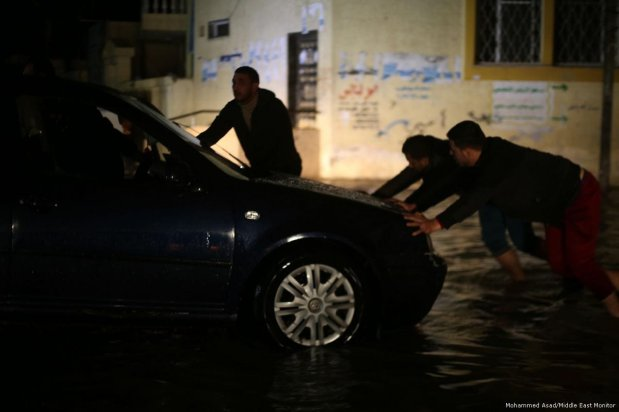 Gazans attempt to move a car after heavy rainfall caused the roads to be blocked on 27 November 2017 [Mohammed Asad/Middle East Monitor]