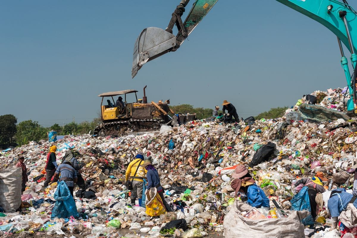 People can be seen sorting through a landfill [Thibaud Saintin/Flickr]