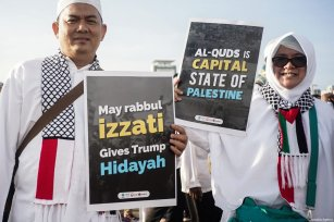 "Protesters show posters reading ""Let Trump get englightment and Al-quds is Palestine capital"" in the demonstration to support Palestine at National Monument in Jakarta, Indonesia on December 17, 2017 [Nani Afrida / Anadolu Agency]"