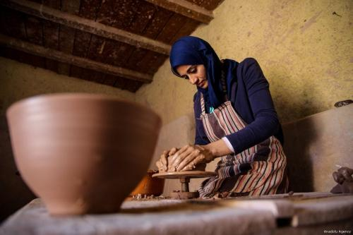 An Egyptian woman shapes a pot out of clay