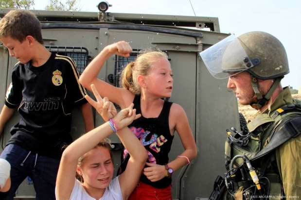 Photo dated in November, 2012 shows Palestinian girl Ahed al-Tamimi (C) challenging Israeli soldiers during a protest in Ramallah, West Bank [QAIS ABUSAMRA/Anadolu Agency]