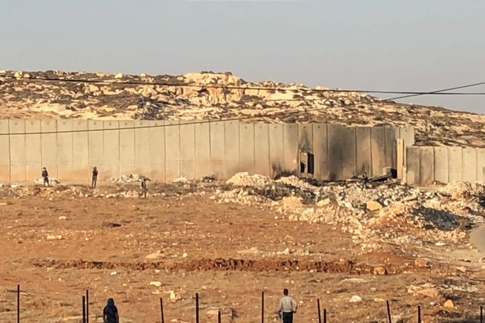 Youths demolished the iron gate built in to the illegal Separation Wall in the village of Anata, northeast of Jerusalem on 1 December 2017. [Safa/Twitter]