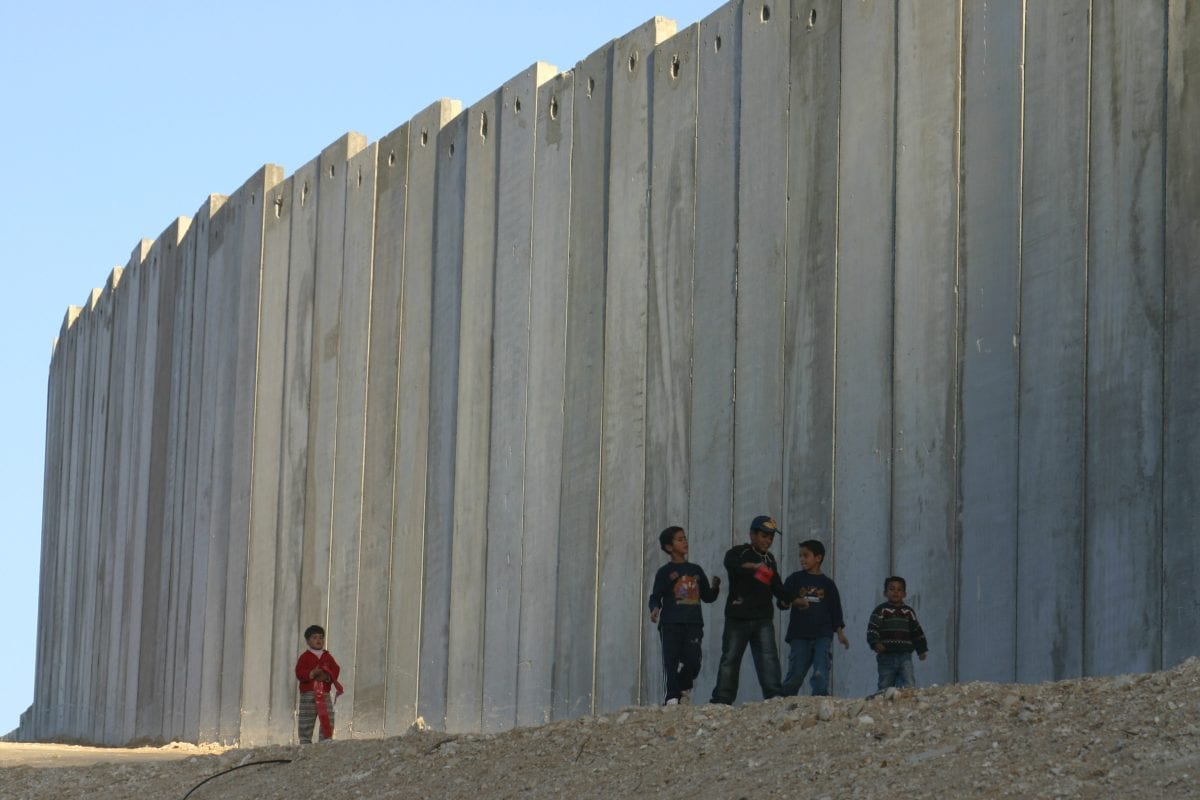 Palestinian children seen along a stretch of the Israeli Seperation Barrier that criss-crosses the occupied West Bank