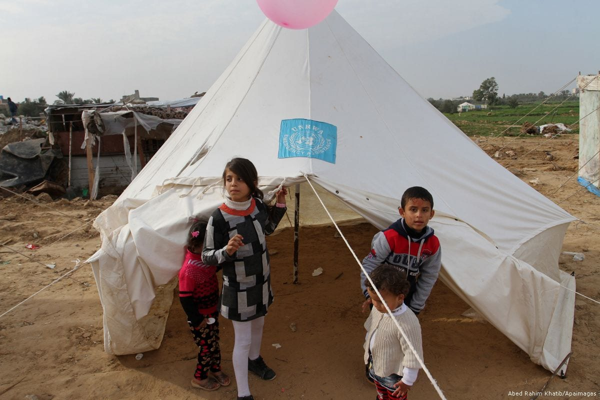 Palestinian children play outside tents set up by UNRWA in Gaza [Abed Rahim Khatib/Apaimages]