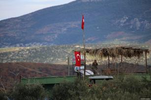 People hang Turkish flags in Sugedigi neighbourhood of Hassa district in Hatay, Turkey on January 19, 2018. Ten busses carrying commandos to reinforce the border units arrived in Hatay [Cem Genco / Anadolu Agency]