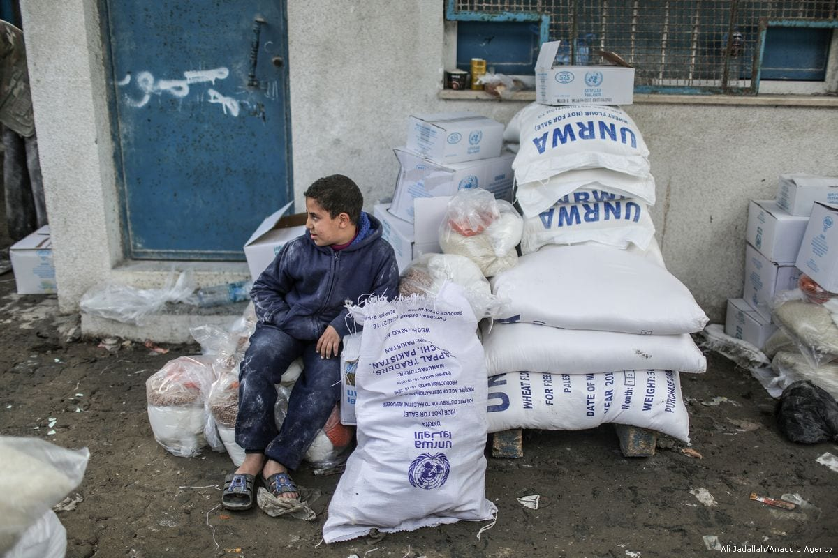 A boy sits near the sacks of flours during a food aid distribution by the United Nations Relief and Works Agency for Palestine Refugees in the Near East (UNRWA) at Al-Shati Refugee Camp in Gaza City, Gaza on January 15, 2018. ( Ali Jadallah - Anadolu Agency )