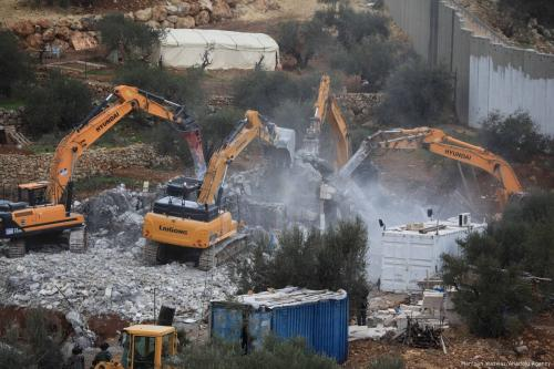 Bulldozers demolish two buildings belongs to Palestinians under the observation of Israeli forces with the claim of unauthorized construction, near Bethlehem, West Bank on January 29, 2018. ( Mamoun Wazwaz - Anadolu Agency )