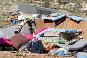 A Syrian women can be seen outside her makeshift home in a refugee camp that hosts displaced Syrians [Muhammed Abdullah/Anadolu Agency]