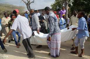People carry the body of the victims after two attacks carried out bomb-laden vehicles near Somalian National Intelligence and Security Agency (NISA) building in Mogadishu, Somalia on February 24, 2018 [Sadak Mohamed / Anadolu Agency]