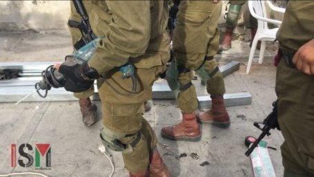 Israeli forces seen at the home of the the Sharabati family, on Shuada street in Hebron, preventing them from performing construction work on their roof for which they had Israeli permission, in February 2018 [ISM]
