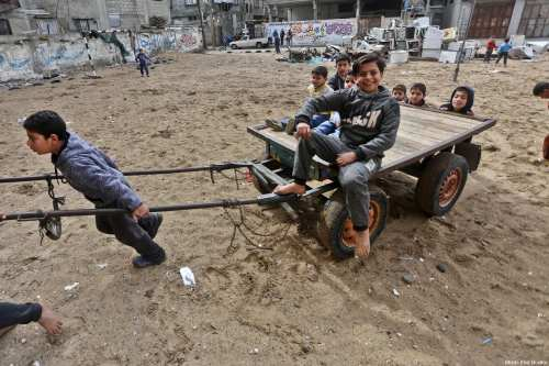 Gazan children seen going about their lives after a day of rain, February 17, 2018 [Mohammed Asad / Middle East Monitor]