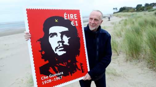 Irishartist Jim Fitzpatrick with a promotional image of a stamp featuring his world famous image of Che Guevara [Irish Times]