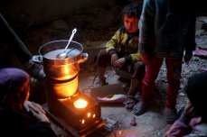 Syrian try to warm themselves with a heating stove in a shelter in Eastern Ghouta of Damascus, Syria on 27 February 2018 [Anas Aldamashqi/Anadolu Agency]