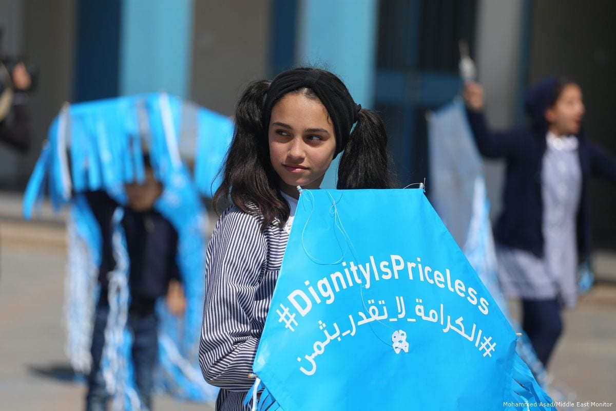 School children in an UNRWA institute fly kites carrying the hashtag 'dignity is priceless' to highlight the dire situation in Gaza [Mohammed Asad/Middle East Monitor]
