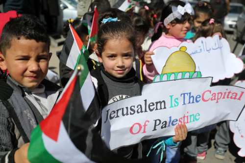 Palestinian children hold banners during a protest against U.S. President Donald Trump's decision to recognise Jerusalem as the capital of Israel, in Gaza city on 28 February, 2018 [Ashraf Amra/Apaimages]