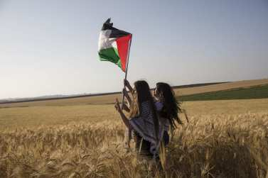 """Members of """"Coalition of Women for Peace"""" consisting Israeli and Palestinian activists hold a Palestinian flag during a protest held to support the """"Great March of Return"""" near the Gaza border in Sderot, Israel on 31 March, 2018 [Stringer/Anadolu Agency]"""