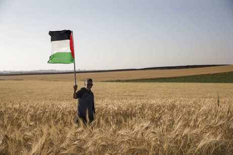 """A man holds a Palestinian flag as members of """"Coalition of Women for Peace"""" consisting Israeli and Palestinian activists stage a protest to support the """"Great March of Return"""" near the Gaza border in Sderot, Israel on 31 March, 2018 [Stringer/Anadolu Agency]"""