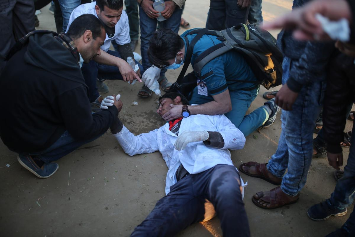 "A medical staff lies on the ground after he was affected by tear gas as Palestinians stage a demonstration demanding the right of return and removal of the blockade following the ""Great March of Return"" in Khan Yunis, Gaza on 1 April, 2018 [Mustafa Hassona/Anadolu Agency]"