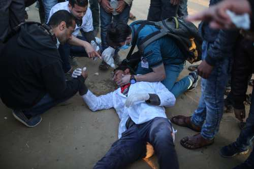 """A medical staff lies on the ground after he was affected by tear gas as Palestinians stage a demonstration demanding the right of return and removal of the blockade following the """"Great March of Return"""" in Khan Yunis, Gaza on 1 April, 2018 [Mustafa Hassona/Anadolu Agency]"""