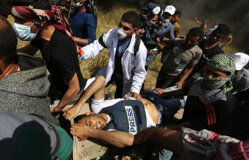 """Palestinians carry the injured Yassser Murtaja (30), shot in the abdomen by the Israeli military while wearing a """"PRESS"""" jacket at the """"Great March of Return"""" on the Gaza border east of Khan Yunis, Gaza on April 06, 2018 [Ashraf Amra / Anadolu Agency]"""