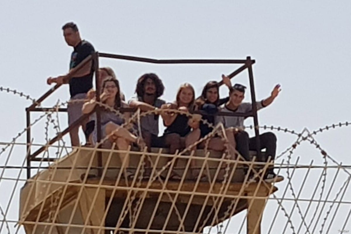 A photo of young Israelis sitting atop a watchtower at the Gaza border and cheering as Israeli forces fired at Palestinian protesters on April 2018 [Twitter]