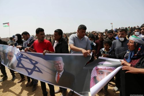 Palestinians burn an Israeli flag and portraits of Trump, Mohammed bin Salman, Avigdor Lieberman and Netanyahu during a tent city protest where Palestinians demand the right to return to their homeland, at the Israel-Gaza border, in Khan Younis in the southern Gaza Strip, April 13, 2018. [Ashraf Amra/Apa Images]