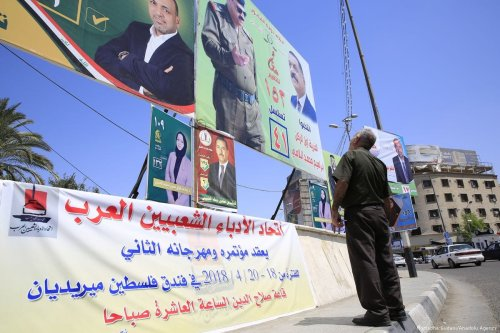 An Iraqi man looks at the candidates' electoral campaign posters ahead of the parliamentary elections, in Baghdad, Iraq on 17 April 2018 [Murtadha Sudani/Anadolu Agency]