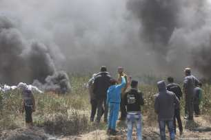 Palestinian protesters take cover afte Israeli forces fire at Palestinian protesters during the 'Great March Of Return' on 6th April 2018 [Mohammed Asad/Middle East Monitor]