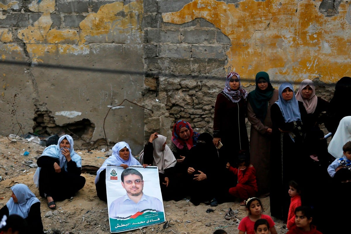 A Palestinian mourner holds a poster of Palestinian scientist Fadi Al-Batsh, assassinated in Malaysia, after his body was returned to his native Gaza Strip on 26 April 2018 [MOHAMMED ABED/AFP via Getty Images]