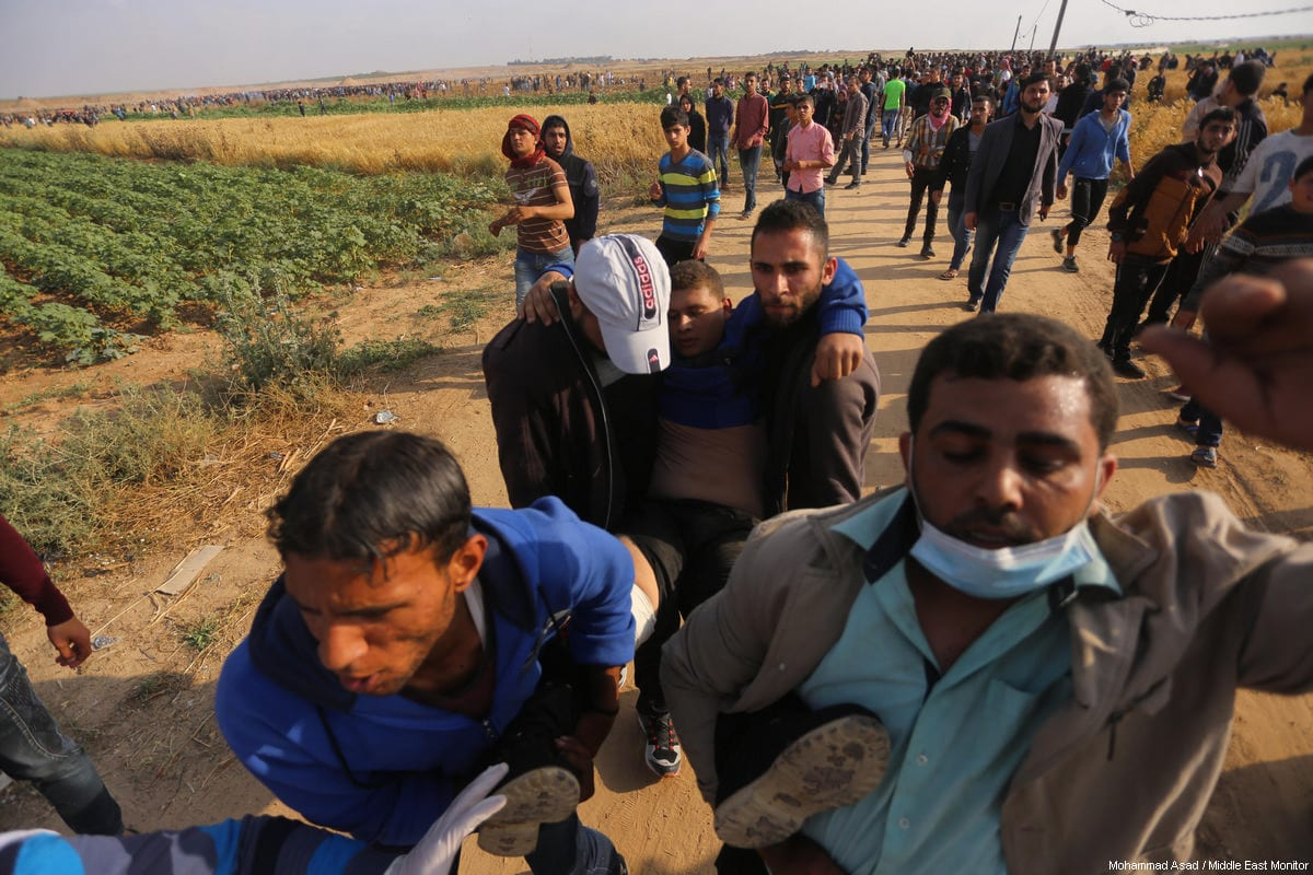 Palestinians carry an injured protestor at the Gaza-Israel border as part of the fifth week of the Great March of Return on April 27, 2018 [Mohammad Asad / Middle East Monitor]