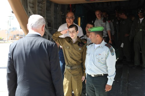 Freed Israeli soldier Gilad Shalit salutes Israel Prime Minister Benjamin Netanyahu after landing in an Israeli army air base. Shalit was released on October 18 2011 after being held as a prisoner of war for five and a half years in the occupied Gaza Strip [IDF Online]