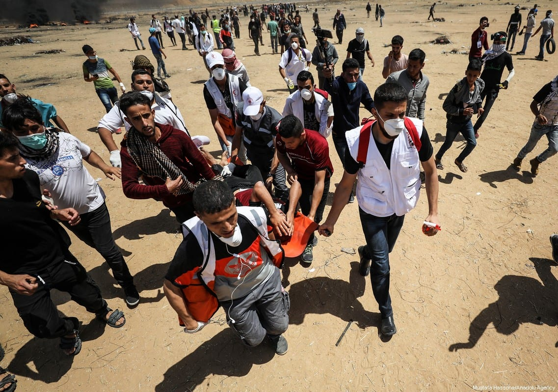 "A Palestinian is wounded during a demonstration as part of the ""Great March of Return"" as smoke rises near Gaza-Israel border in Khan Yunis, Gaza on 11 May 2018. [Mustafa Hassona/Anadolu Agency]"
