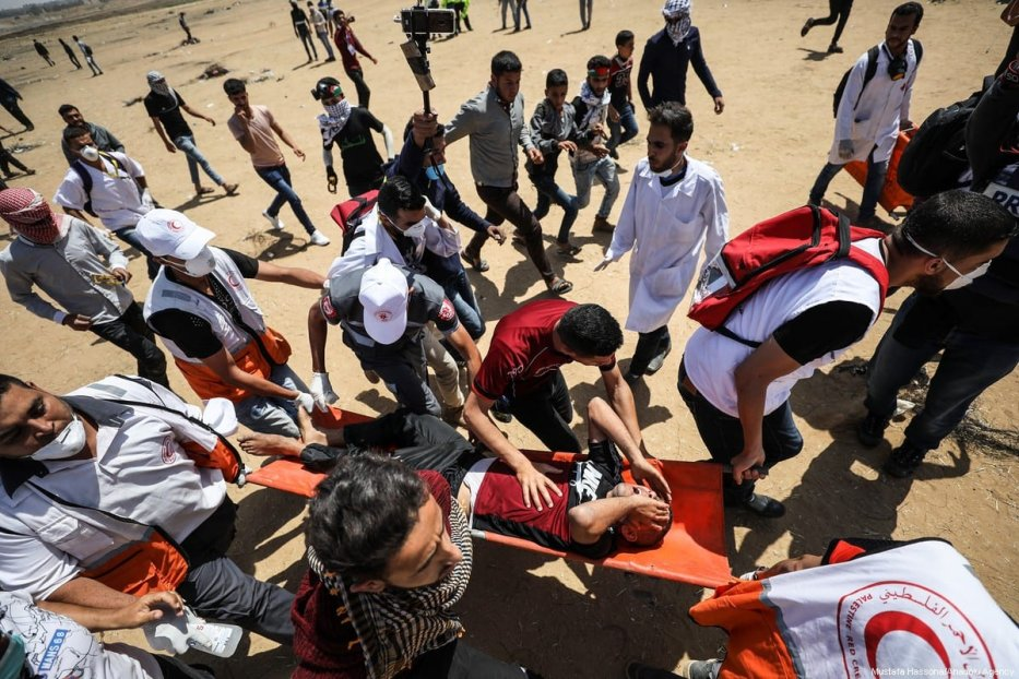 "A wounded Palestinian demonstrator is carried by health team members after getting injured on intervention of Israeli occupation forces during a demonstration within the ""Great March of Return"" in Khan Yunis, Gaza on 11 May 2018. [Mustafa Hassona/Anadolu Agency]"