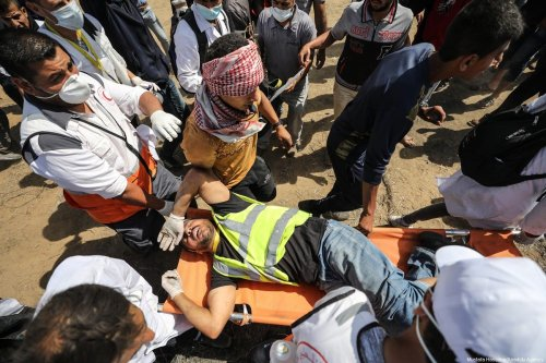 """A wounded Palestinian demonstrator is carried by health team members after getting injured on intervention of Israeli occupation forces during a demonstration within the """"Great March of Return"""" as smoke rises near Gaza-Israel border in Khan Yunis, Gaza on 11 May 2018. [Mustafa Hassona/Anadolu Agency]"""