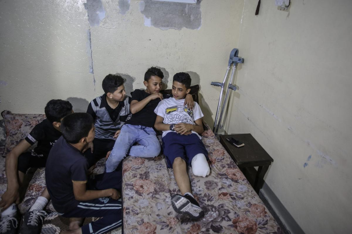 """11-year-old Gazaian Abdurrahman Nevfel (R), who lost his leg after Israeli soldiers opened fire on """"Great March of Returns"""" demonstrations at Gaza Strip, is seen with his crutch in Gaza City, Gaza on 12 May, 2018 [Ali Jadallah/Anadolu Agency]"""