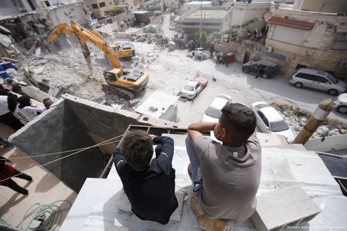 Palestinian boys watch as Israeli excavators demolish a Palestinian apartment block for allegedly being unauthorised in East Jerusalem on 1 May 2018 [Mostafa Alkharouf/Anadolu Agency]