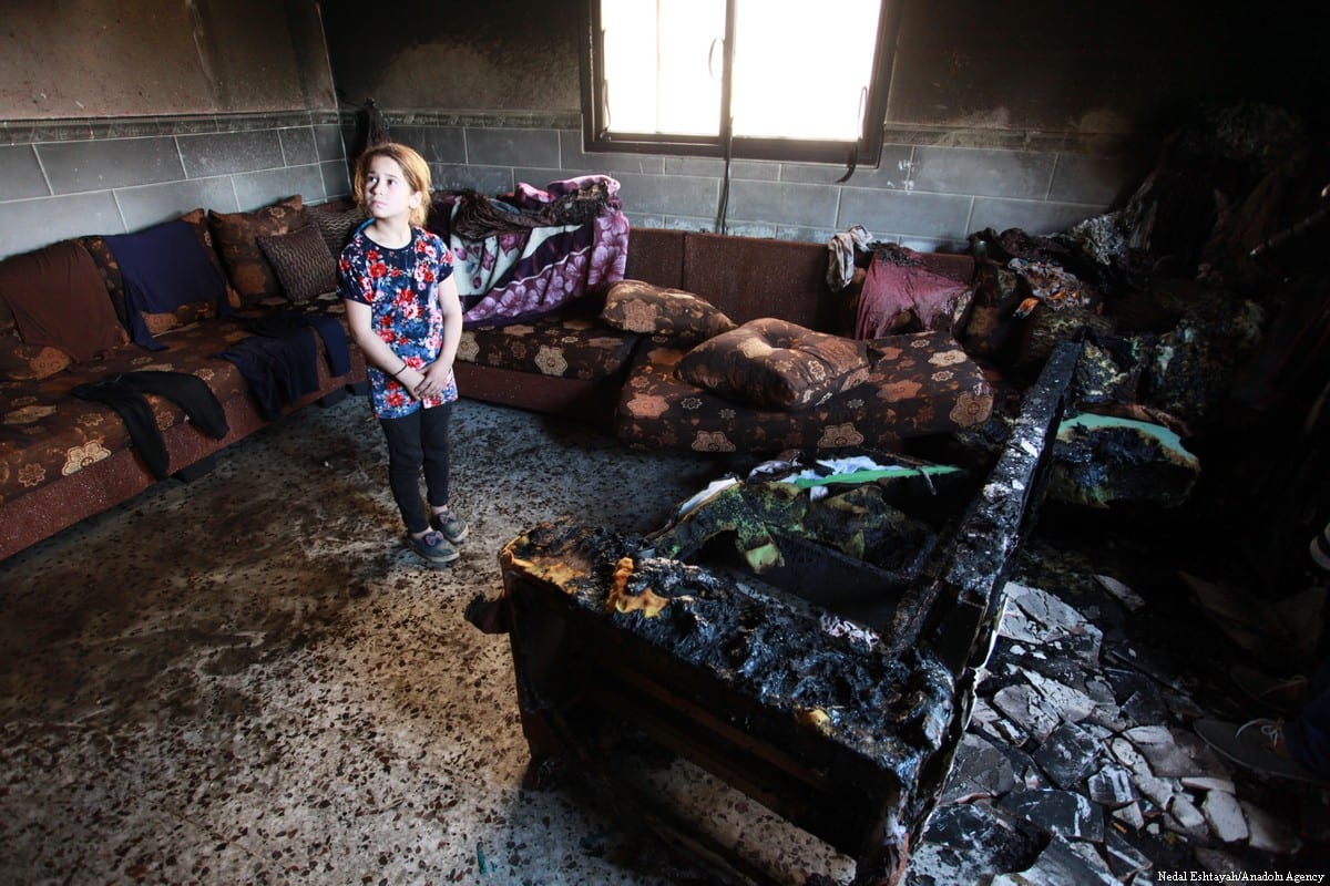 A Palestinian girl stands in her living room after it was set alight by Jewish settlers in the West Bank on 11 May 2018 [Nedal Eshtayah/Anadolu Agency]