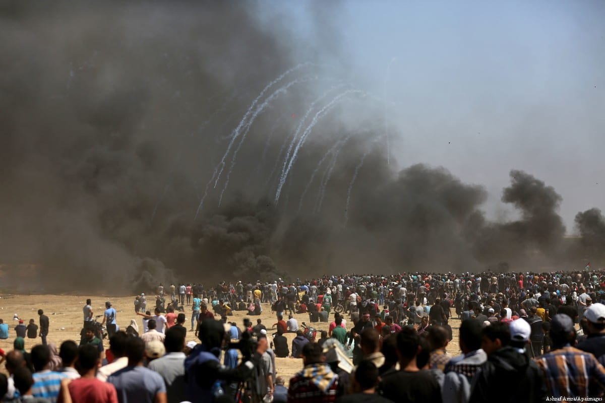 """Palestinian protesters gather during clashes with Israeli security forces in a tent city protest where Palestinians demand the right to return to their homeland, on the occasion of the 70th anniversary of the """"Nakba"""", and against U.S. embassy move to Jerusalem at Israel-Gaza border at the Israel-Gaza border, in east of Gaza city on 14 May, 2018 [Ramez Habboub/Apaimages]"""