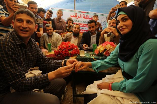 Palestinian couple Muaz Rukup and Hedil Naccar, medical officials who had worked during 'Great March of Return' are seen during their wedding ceremony in Gaza on 2 May 2018 [Abed Rahim Khatib/Anadolu Agency]