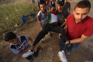 An injured Palestinian is being carried away after Israeli forces attacked Palestinian protesters at the Gaza and Israel border on 25 May 2018 [Mohammad Asad / Middle East Monitor]