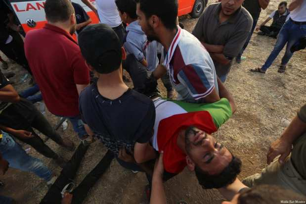 An injured Palestinian is seen taken away as Israeli forces clash with Palestinian protesters at the Gaza and Israel border during the ninth consecutive week of protests, organised as part of the Great March of Return, on 25 May 2018 [Mohammad Asad / Middle East Monitor]
