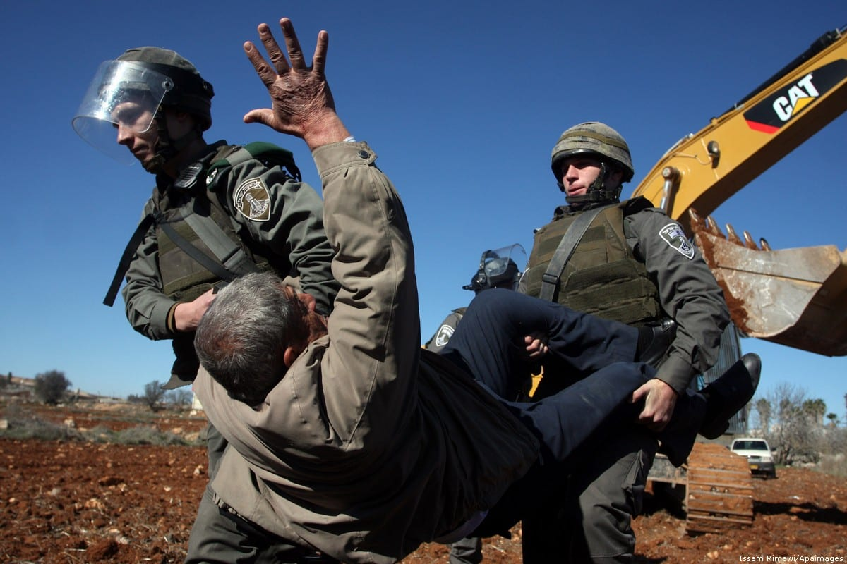 A Palestinian man is carried by Israeli border police officers in the West Bank village of Qaladiya near Ramallah [Issam Rimawi/Apaimages]