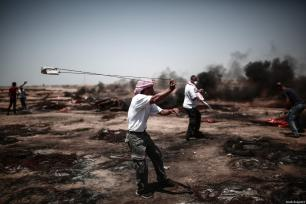 """Palestinians use slingshot to throw stones during the protests called """"commemorating the Naksa"""", along the border fence, east of Khan Yunis in the southern Gaza Strip on June 8, 2018 [Mustafa Hassona / Anadolu Agency]"""