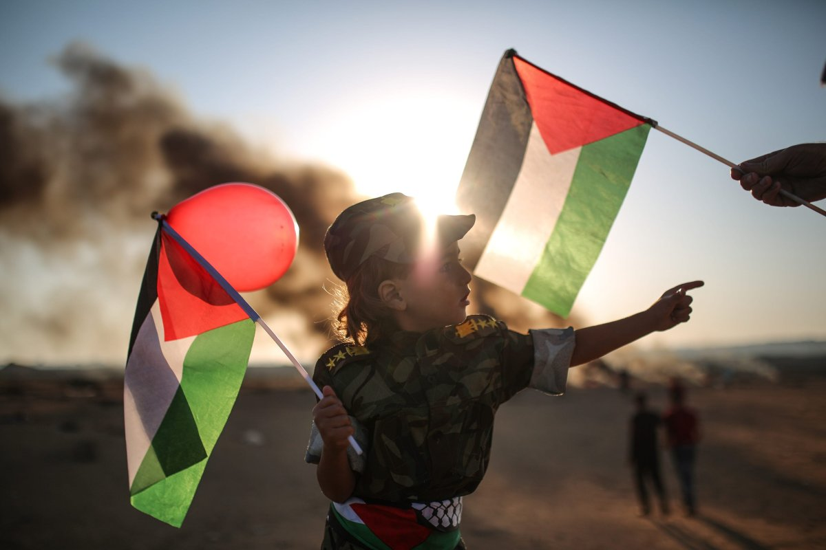 A Palestinian woman with her child marches towards Israeli border during the first day of Eid al-Fitr in Khan Yunis, Gaza on 15 June, 2018 [Mustafa Hassona/Anadolu Agency]