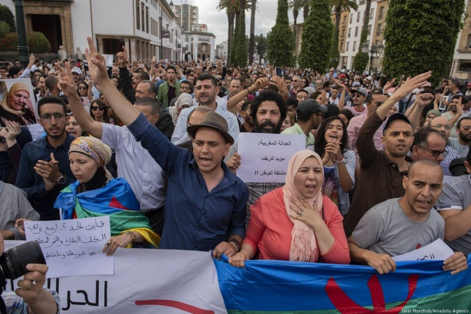A group of people hold banners during a demonstration against the prison sentence for Rif Movement leader Nasser Zefzafi and members along with him, in front of the parliament building in Rabat, Morocco on 27 June 2018 [Jalal Morchidi/Anadolu Agency]